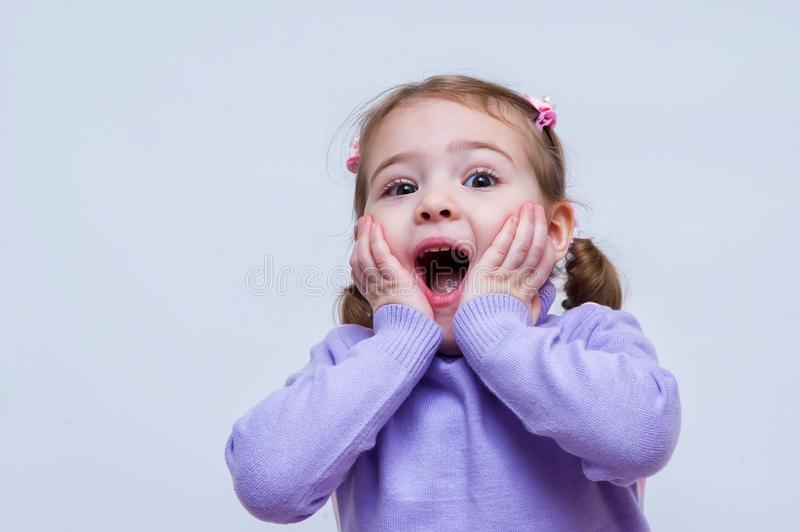 Surprised baby girl and put her hand on the head royalty free stock image