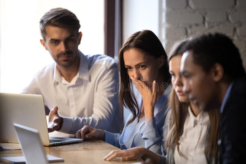 Surprised baffled diverse colleagues received bad news by email. Group diverse surprised colleagues sitting at desk looking at computer screen looks feels stock image
