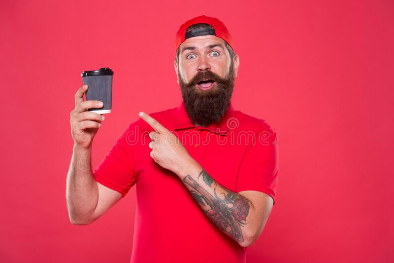 Surprised barista coffee cup. take away coffee here. best quality of cafe service stuff. good morning coffee to go. Bearded man drink tea red background royalty free stock image