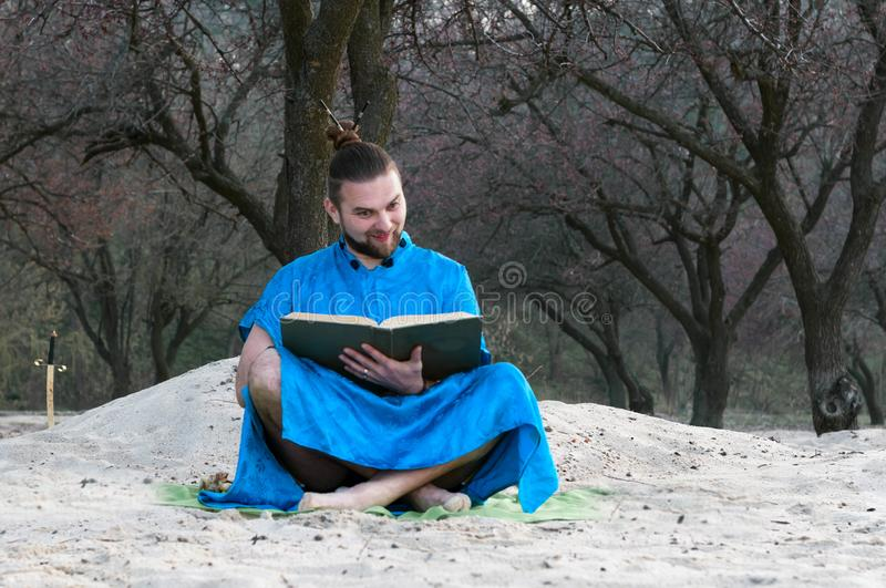 Surprised bearded man in blue kimono sitting with large book on sandy beach royalty free stock image