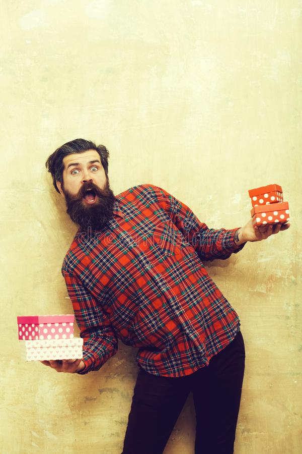 Surprised bearded man holding colorful gift boxes stacked in hands stock photo