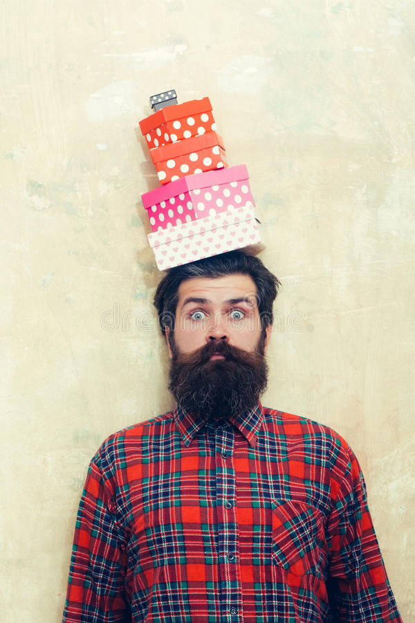 Surprised bearded man holding colorful gift boxes stacked on head stock image