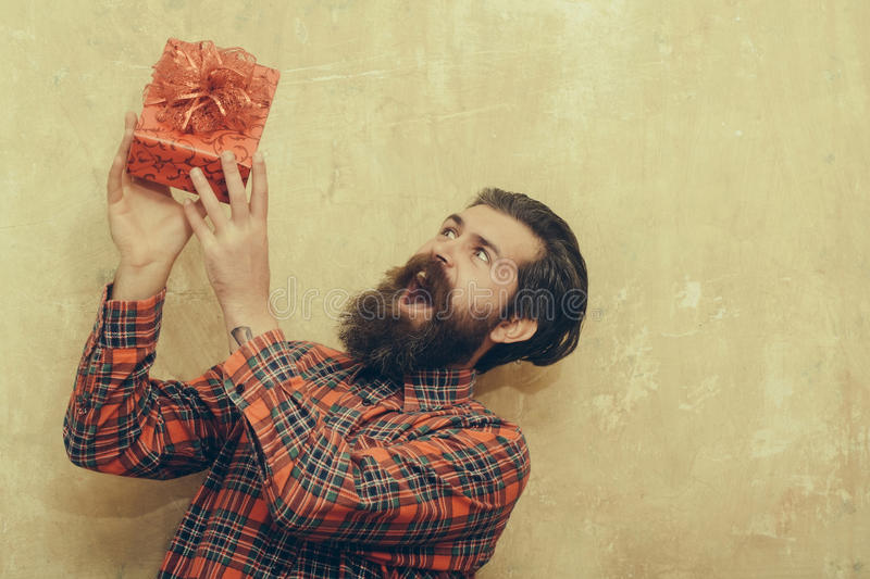 Surprised bearded man holding red gift box with bow stock photo