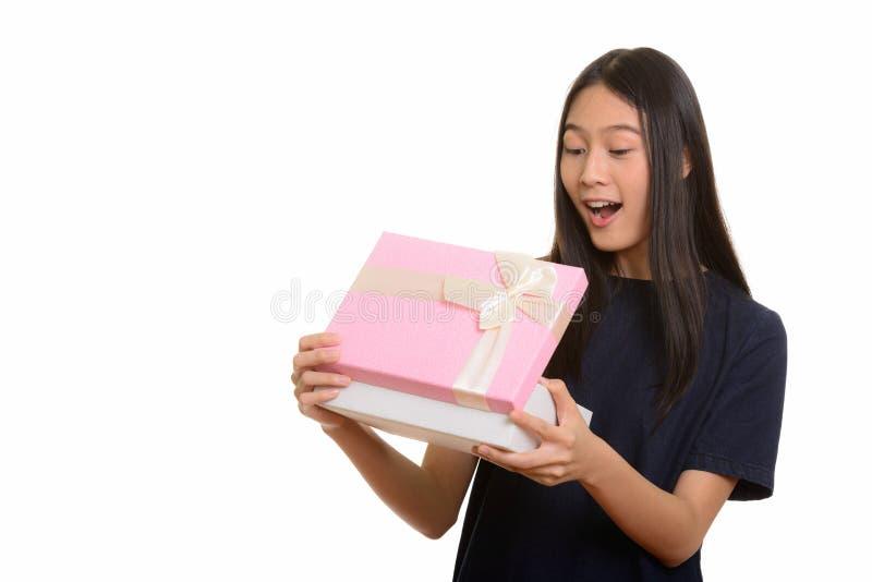 Surprised beautiful Asian teenage girl opening gift box royalty free stock photo