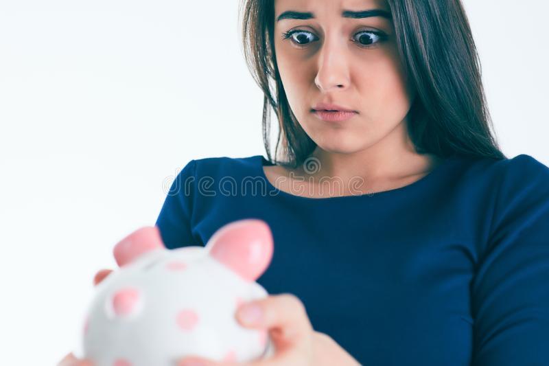 Surprised beautiful Caucasian brunette woman holding a piggybank. stock photo