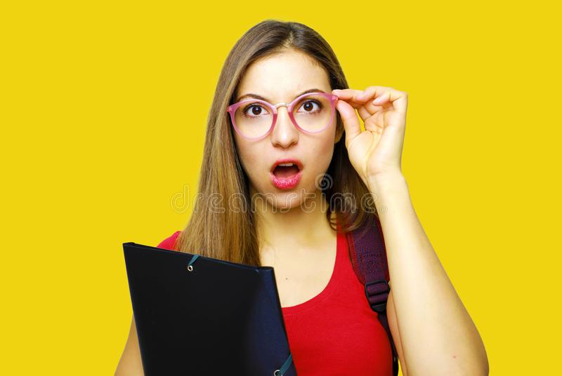 Surprised beautiful student girl. Young shocked student woman holding folder on yellow background royalty free stock images