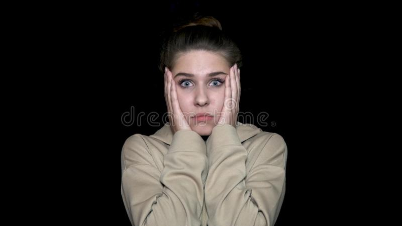 Surprised beautiful woman holds cheeks by her hands, isolated on black background. Young woman shocked stock photo