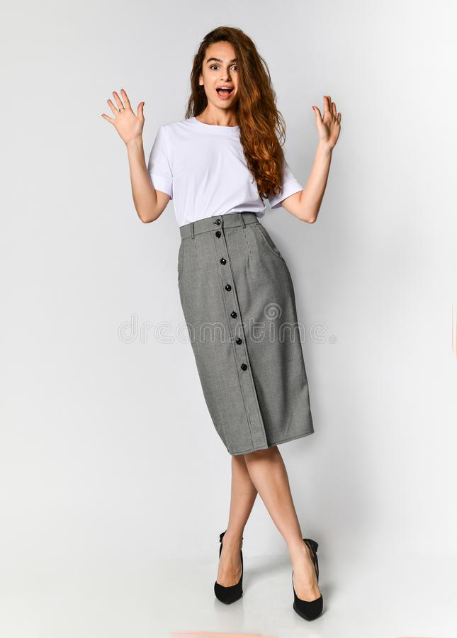 Surprised beautiful woman posing in a new white blueska and gray skirt with buttons, spread her arms to the side of what she saw stock photos