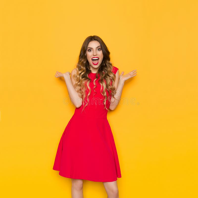 Surprised Beautiful Woman In Red Dress With Arms Outstretched Is Shouting royalty free stock image