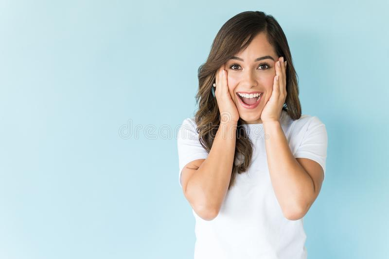 Surprised Beautiful Woman In Studio. Astonished female model with head in hands  on plain background stock photos