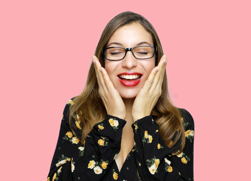 Surprised beautiful young woman holds cheeks by hand and wear glasses with closed eyes.  royalty free stock photo