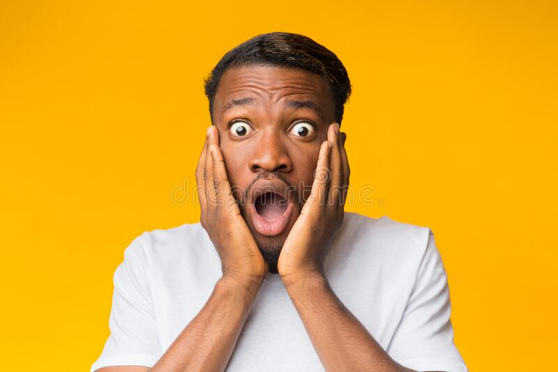 Surprised Black Man Touching Face Posing Over Orange Background. Omg. Surprised Black Man Touching Face Looking At Camera In Shock Posing Over Orange Background royalty free stock photography