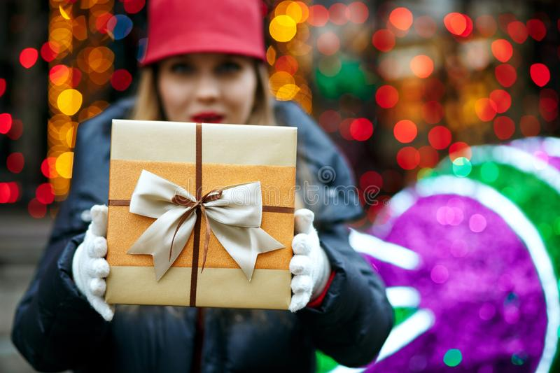 Surprised blonde girl wearing trendy cap and holding gift box wi stock photography