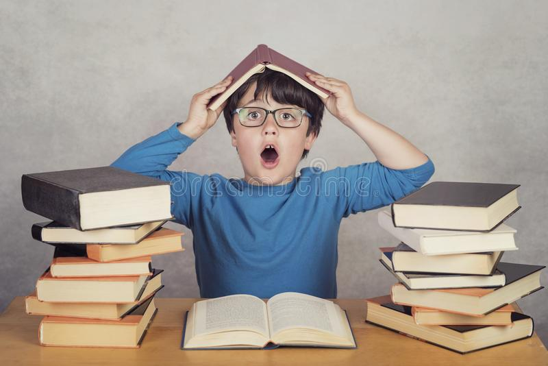 Surprised boy with books on a table stock photos