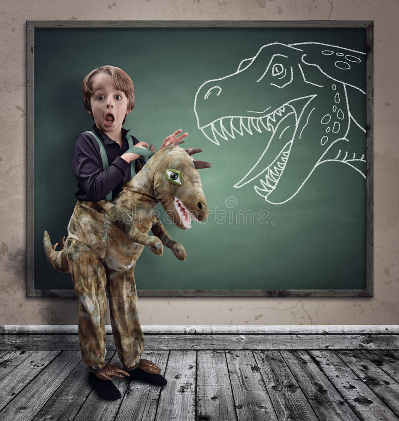 Surprised boy dressed in fancy dress as a dinosaur. With chalk tyrannosaurus rex on blackboard concept for education, history, science and imagination stock illustration