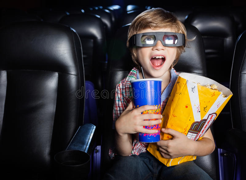 Surprised Boy Watching 3D Movie In Theater. Surprised boy holding snacks while watching 3D movie in cinema theater stock photography