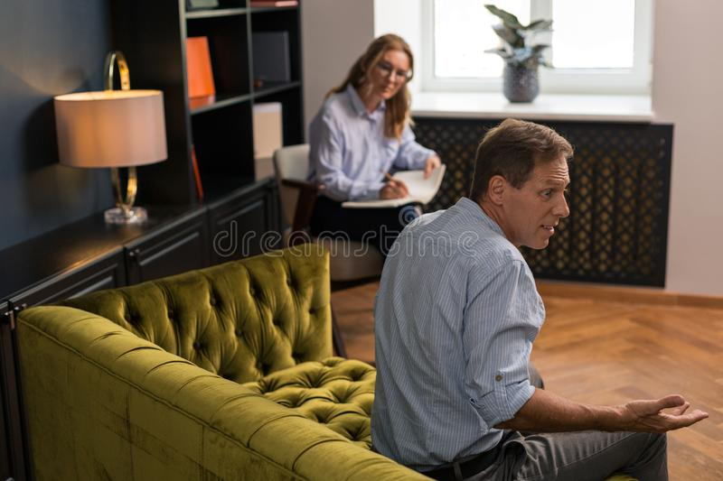 Surprised brown-haired middle-aged man sitting on the couch. Astonished expression. Surprised brown-haired middle-aged men sitting on the couch in the stock photography