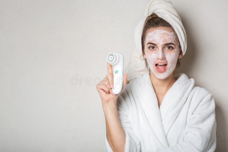 Surprised brunette girl posing with moisturizing cream mask and face cleaner. Empty space. Surprised brunette woman posing with moisturizing cream mask and face stock photos