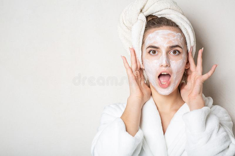 Surprised brunette model with moisturizing cream mask and bath towel on head. Empty space. Surprised brunette woman with moisturizing cream mask and bath towel stock photos