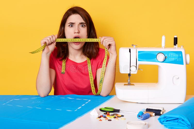 Surprised brunette seamstress holding measure tape in front of her mouth, looking directly at camera. Sewing machine, piece of. Blue fabric, buttons, thread stock photography