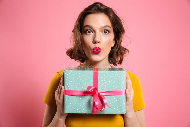 Surprised brunette woman with bright makeup holding present, loo. King at camera, isolated over pink background royalty free stock photography