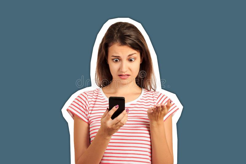 Surprised brunette woman looking at the phone and does not understand what`s going on. emotional girl Magazine collage style with. Trendy color background royalty free stock photography