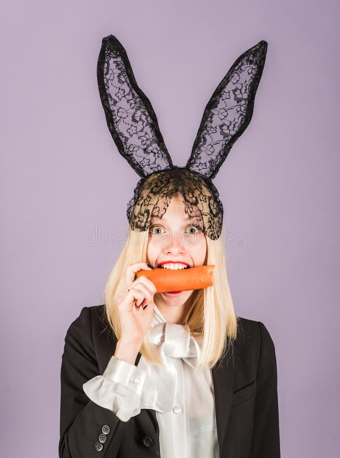 Surprised bunny woman wearing bunny ears and eat carrot. Happy easter and funny easter day. Smile easter. Surprised bunny woman wearing bunny ears and eat stock images