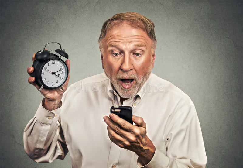 Surprised business man with alarm clock looking at smart phone stock photography