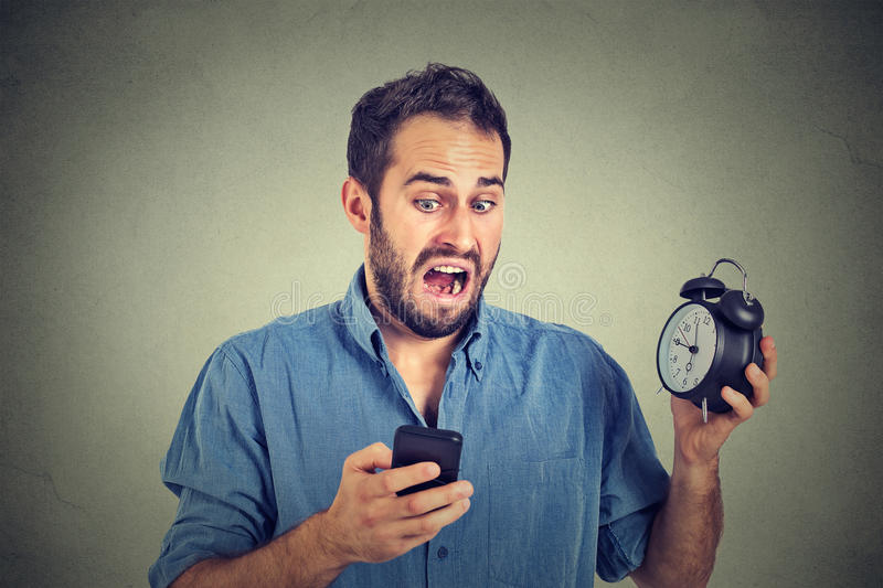 Surprised business man with alarm clock looking at smart phone. Portrait surprised business man with alarm clock looking at smart phone with funny face royalty free stock image