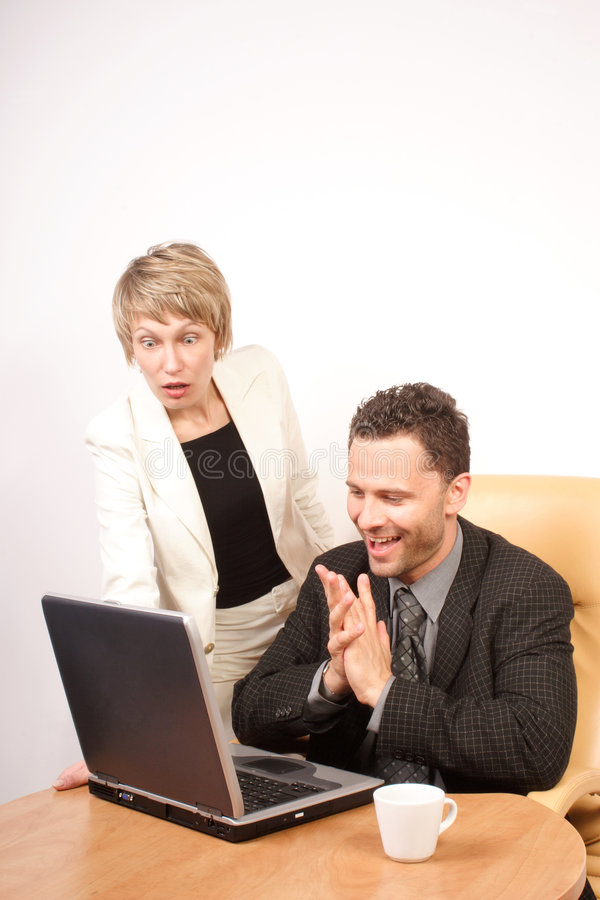 Surprised business woman and joyful business man. Looking at the screen of laptop stock photo