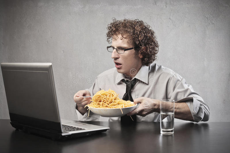 Surprised Businessman Eating. Businessman surprising while eating spaghetti and using a laptop computer stock images