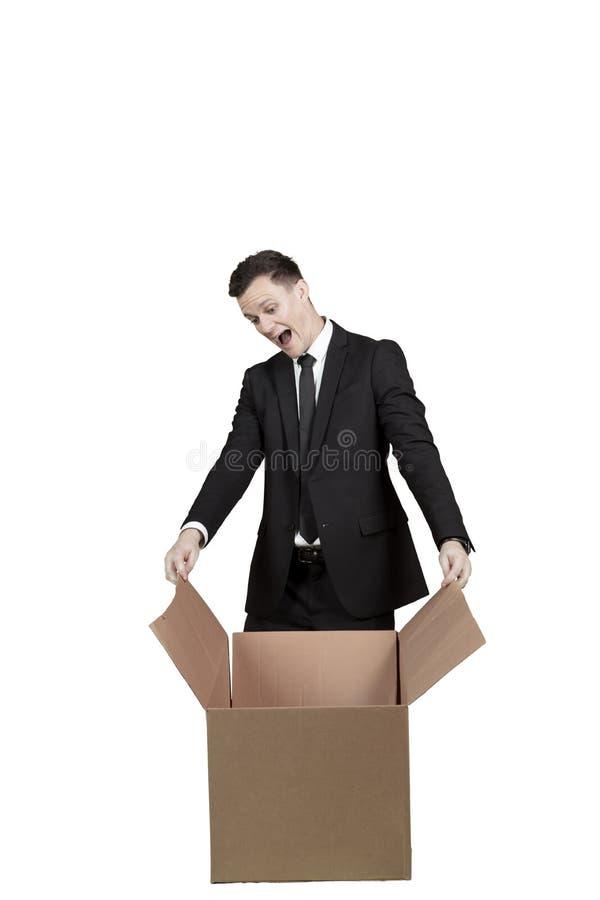 Surprised businessman opens big cardboard stock photo