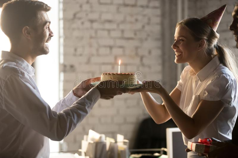 Surprised businessman receiving cake from smiling colleague in party hat stock photos