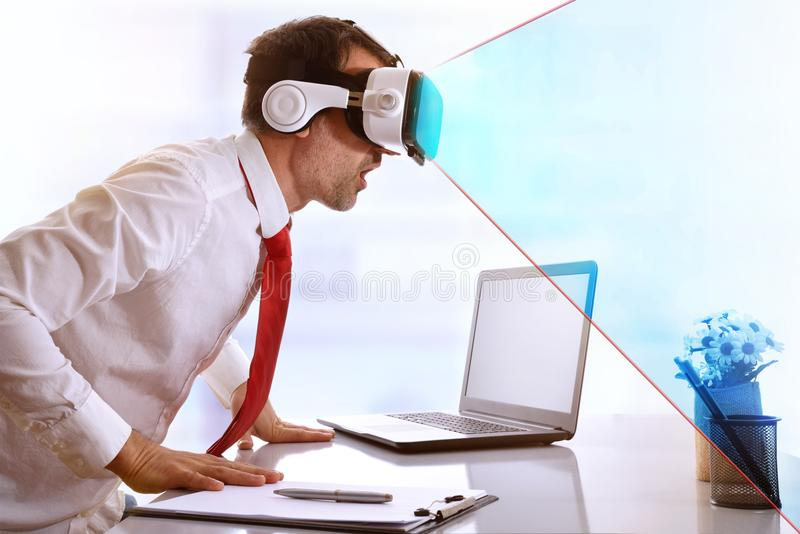 Surprised businessman using virtual reality glasses with blue vi stock photography