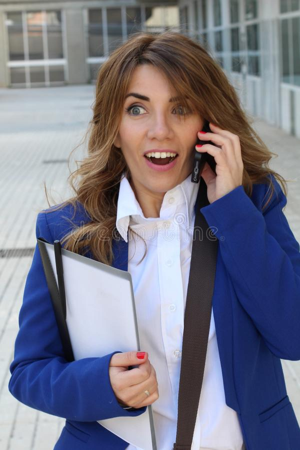 Surprised businesswoman getting great news on the phone stock photography