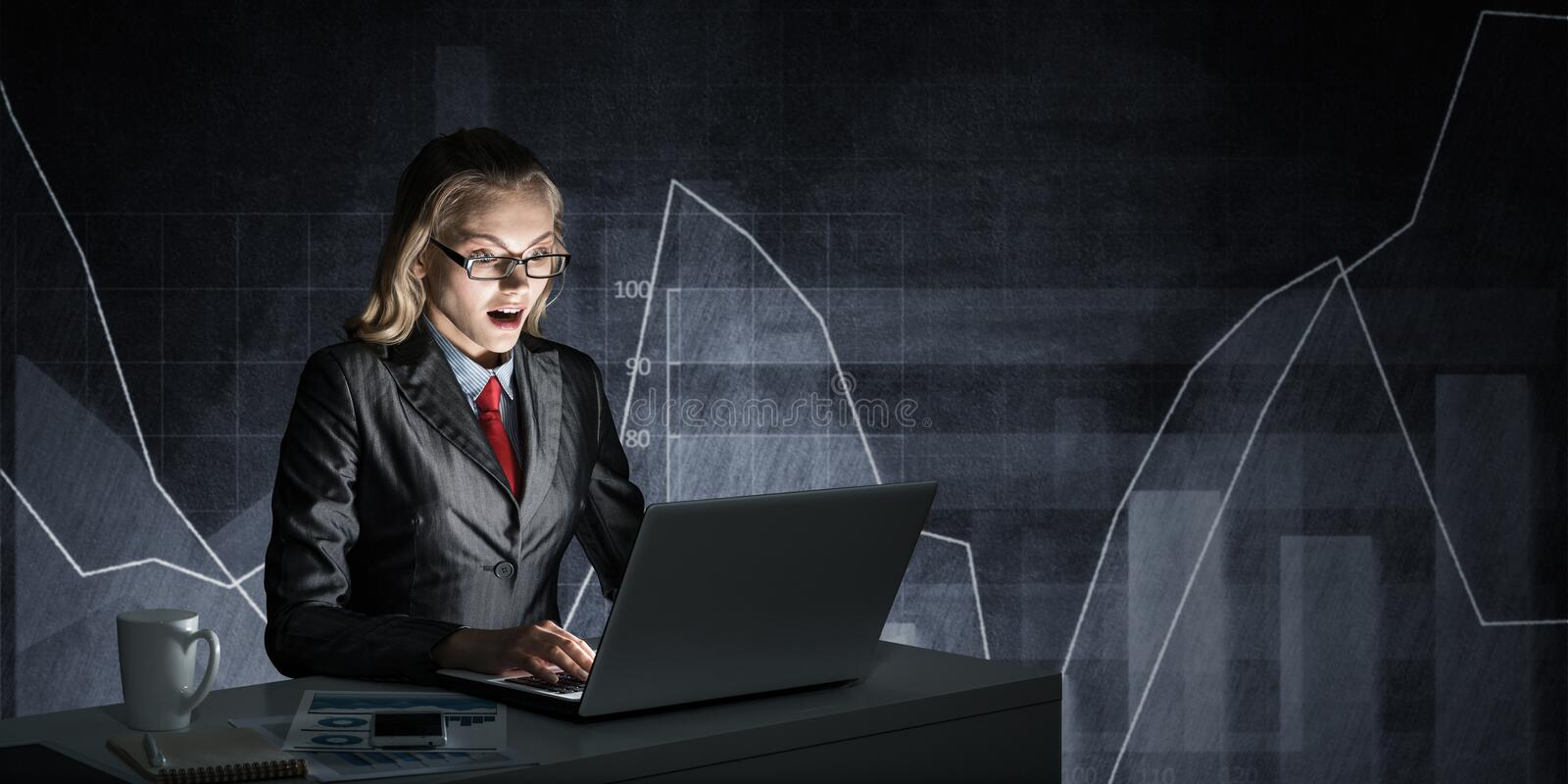 Surprised businesswoman in glasses at office desk. Surprised businesswoman in glasses sitting at office desk and looking at laptop on background grey wall with stock photography