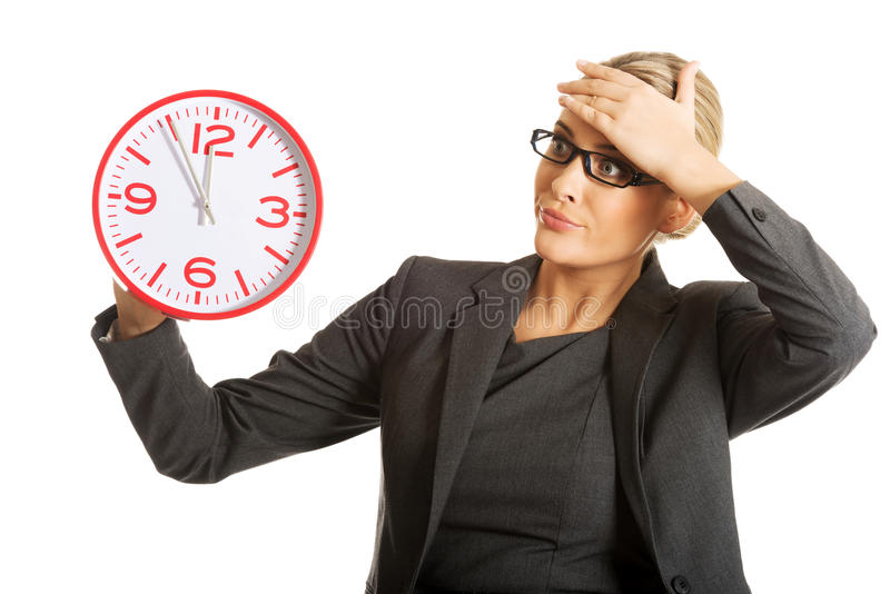 Surprised businesswoman holding a big clock stock image