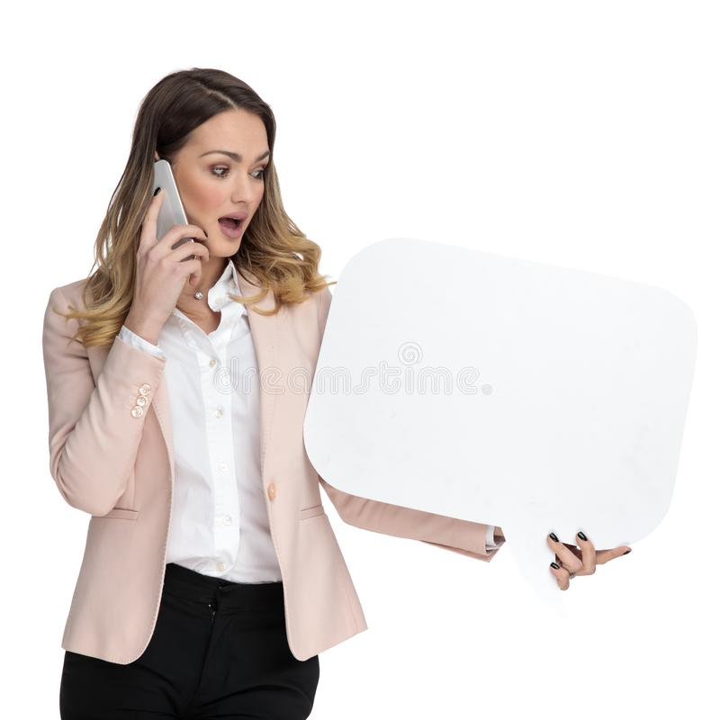 Surprised businesswoman talking on the phone looks at speech bubble stock images
