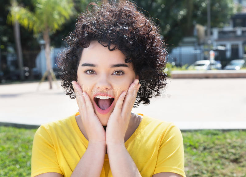 Surprised caucasian girl with curly black hair stock photo