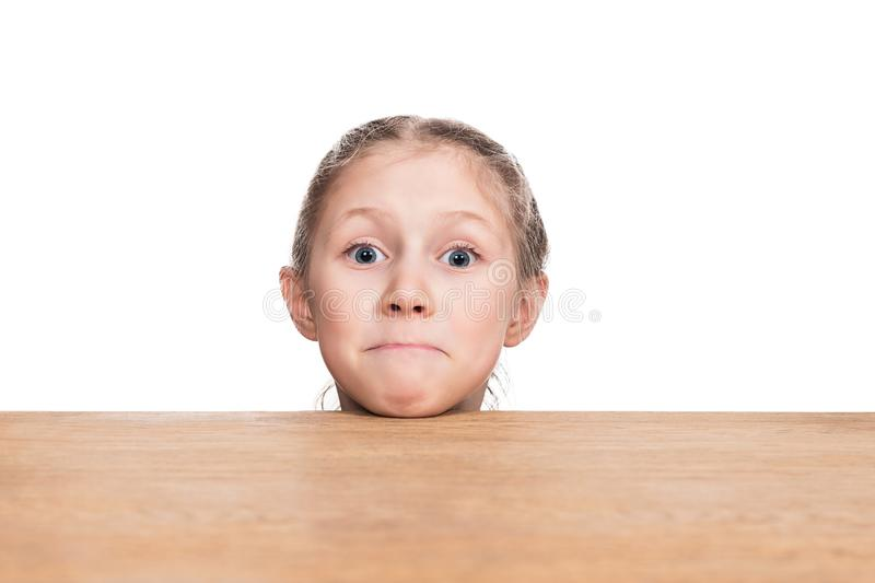 Head on table. Surprised child head climbed out from under a wooden table isolated on white background stock image