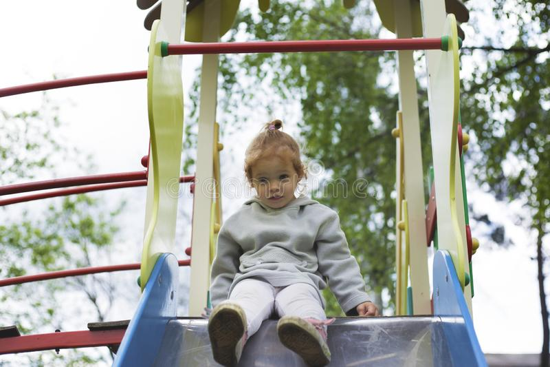Surprised child looking down a children slide stock image