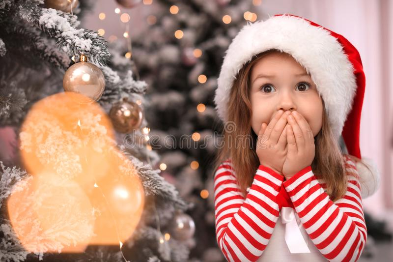 Surprised child near Christmas tree at home royalty free stock images