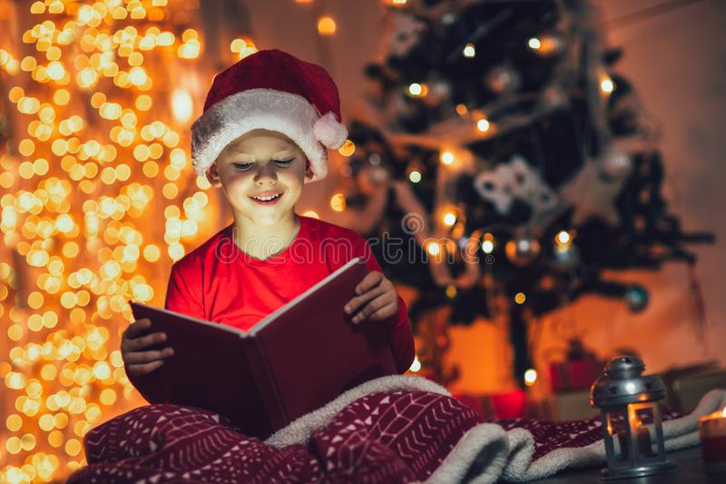 Surprised child opening magic Christmas book. Xmas holiday concept stock images