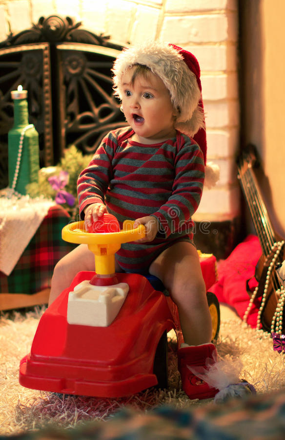 Surprised child in Santa hat is sitting in a baby car. Surprised child in Santa hat is sitting in a baby red car stock photo