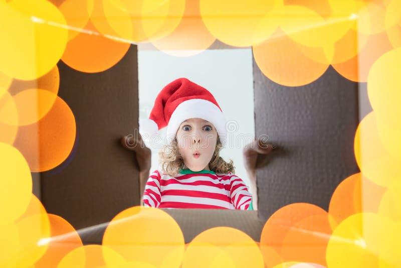 Surprised child unpack Christmas gift box stock photo