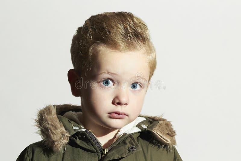Surprised child in winter coat. fashion kid.children.khaki parka.little boy. With big eyes.hairstyle stock photo