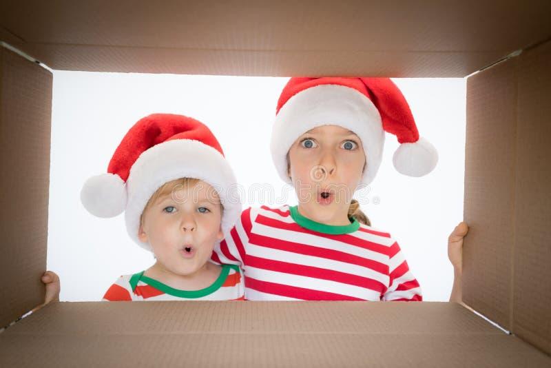 Surprised children unpack Christmas gift box stock photo