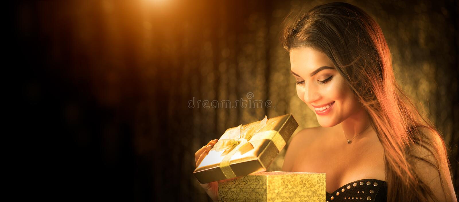 Surprised Christmas Winter Woman opening magic Christmas Gift box and smiling. Fairy tale. Beautiful New Year and Xmas scene royalty free stock image