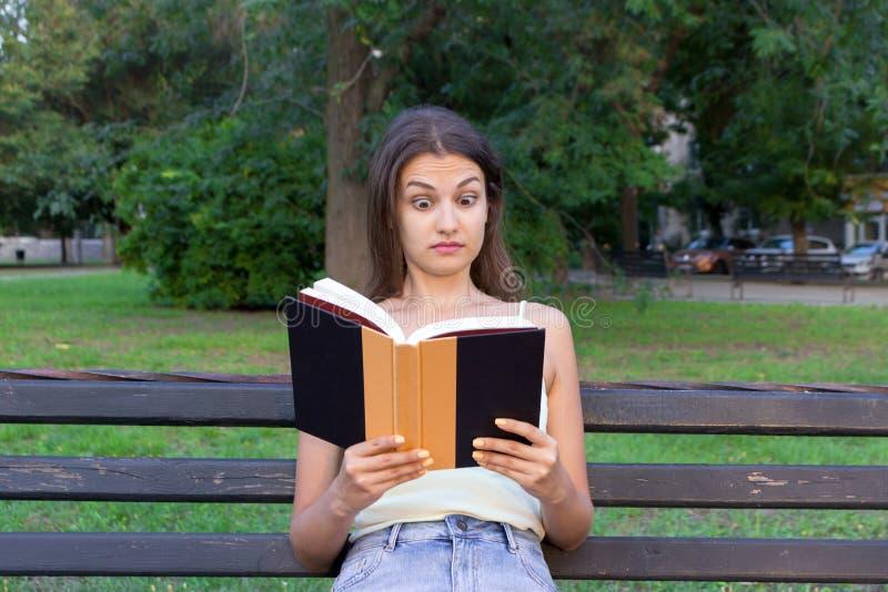 Surprised confundió y con los ojos extensamente abiertos la mujer está leyendo un libro en el banco en el parque imagenes de archivo