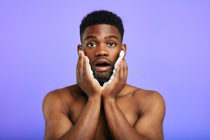 Surprised confundiu o homem com a boca aberta que guarda as m?os nos mordentes imagens de stock royalty free